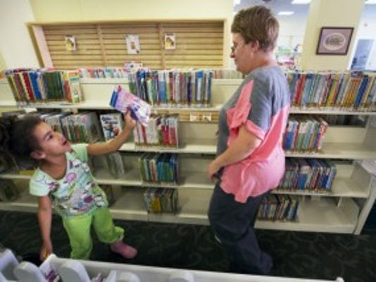 Elizabeth Dell, right, of York, picks out books with her daughter Mariah, 7, at Martin Library. She said that her daughter has read 100 books and she has read 200 books to her son. (Paul Kuehnel - York Daily Record/ Sunday News)