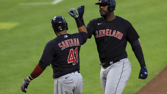 Cleveland Indians' Carlos Santana (41) celebrates the two-run home run hit by Franmil Reyes (32) in the eighth inning during a baseball game against the Cincinnati Reds in Cincinnati, Tuesday, Aug. 4, 2020.