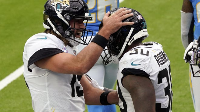 Jacksonville Jaguars quarterback Gardner Minshew, left, celebrates with running back James Robinson after scoring against the Los Angeles Chargers during the first half Sunday's game in Inglewood, Calif.