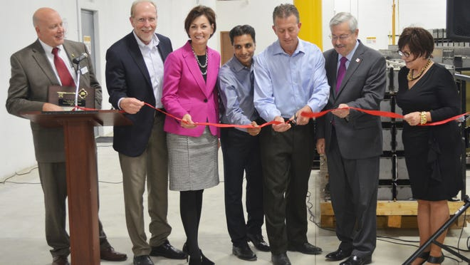 Officials on hand for the ribbon cutting Monday at Zero Energy Systems include, from left, Coralville Mayor John Lundell, Rep. Dave Loebsack, Lt. Gov. Kim Reynolds, company co-founders Manoj Krishan and Scott Long, Gov. Terry Branstad and Iowa Economic Development Director Debi Durham.