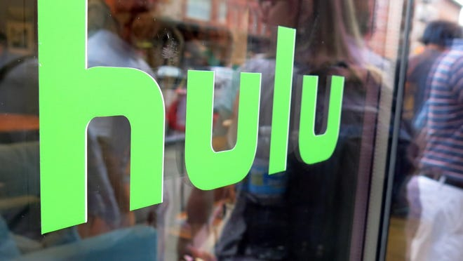 """This Saturday, June 27, 2015, file photo, shows the Hulu logo on a window at the Milk Studios space in New York, where a replica of the """"Seinfeld"""" set was on display. Some television companies are balking as more people watch shows online, and may start delaying the release of shows to streaming services like Netflix and Hulu. These studios fear that the success of streaming services might lead more households to cut back or drop cable TV services. It also comes as online services have been dabbling in creating their own television shows."""