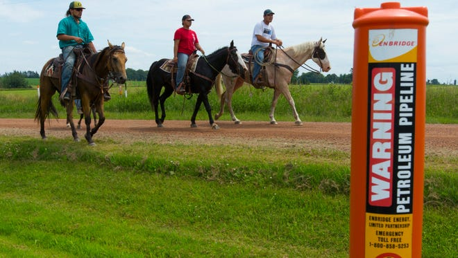 Horse-mounted protesters ride along an underground oil pipeline that carries Canadian tar sands oil south of Owen. About 40 people embarked on the horse trip to draw attention to the possibility of pipeline company Enbridge building a second line.