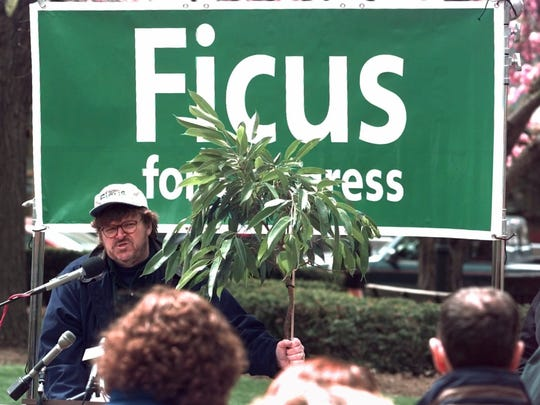 """""""Television personality and filmmaker Michael Moore holds a ficus tree during a tongue-in-cheek news conference in Morristown, N.J., Wednesday, April 26, 2000, to announce the write-in candidacy of the ficus tree for the 11th Congressional District seat, currently held by Republican Rodney Frelinghuysen. Moore says the ficus will run as both a Democrat and a Republican. """"""""There is little difference between the two so-called parties,"""""""" Moore said. (AP Photo/Mike Derer)"""""""