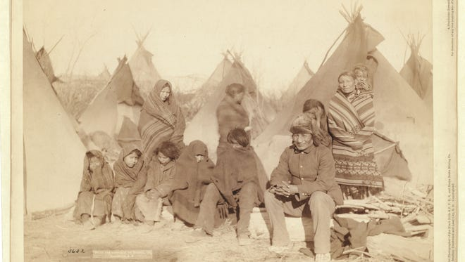 Survivors of the Wounded Knee massacre in South Dakota are pictured in 1891.