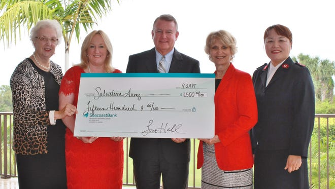 Seacoast Bank Executive Vice President Tom Hall delivers a check to The Salvation Army's Women's Auxiliary as a sponsor of its annual Wings of Hope Luncheon. Pictured with Hall are, from left, Auxiliary President Muriel Franz, Luncheon Co-Chairs Vicki Davis, Martin County supervisor of elections, and Carolyn Timmann and Capt. Christine Kim.