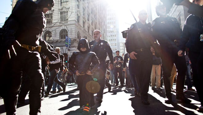 "Police escort 5-year-old leukemia survivor Miles Scott, also known as Batkid, and Batman after they ""arrest"" the Riddler Nov. 15, 2013 in San Francisco."