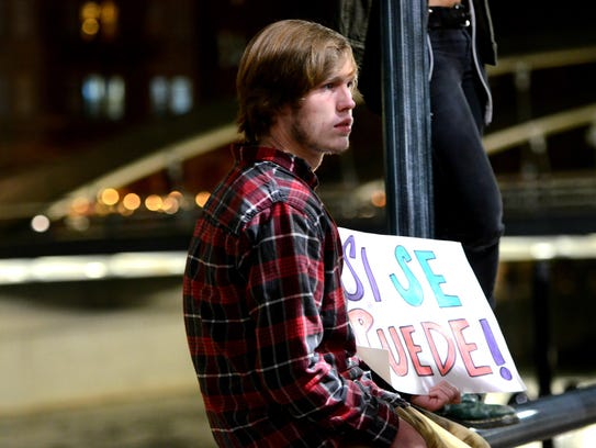 """Fritz Filson, 18, holds a poster that reads """"Si Se"""