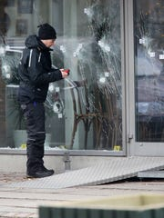 Police investigators work at the scene of Saturday's shooting at a free speech event in Copenhagen, Sunday, Feb. 15, 2015. Danish police shot and killed a man early Sunday suspected of carrying out shooting attacks at a free speech event and then at a Copenhagen synagogue, killing two men, including a member of Denmark's Jewish community. Five police officers were also wounded in the attacks.