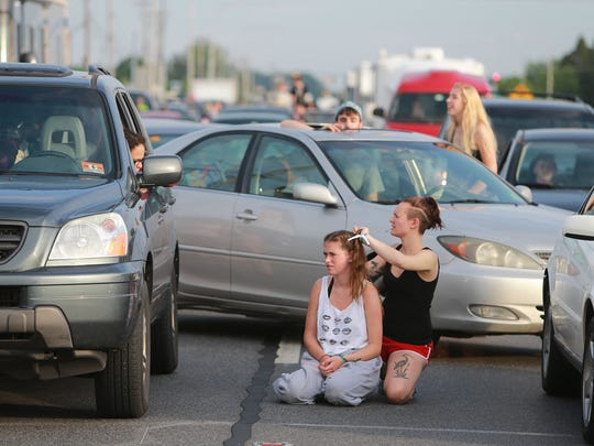 Jamie Wand gets her hair braided by Agata Chrobot as traffic along U.S.13 near Dover International Speedway was at a standstill before Firefly 2014. Traffic has been less of an issue in years since.