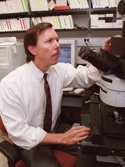 -  -RK Dr. Ralph Nixon using a microscope at the Nathan