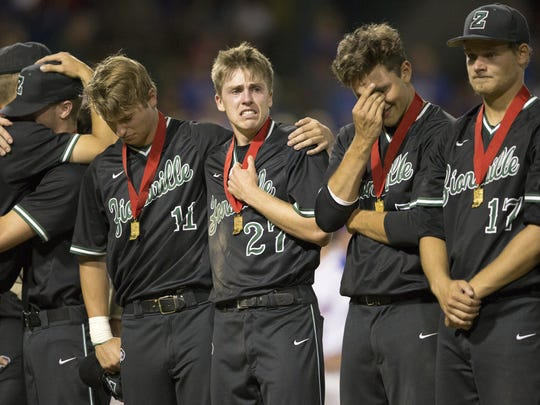 Zionsville High School players react after getting their runner-up medals upon losing a 2-3 extra innings game to Roncalli High School in the 4A baseball title game at Victory Field, Indianapolis, Friday, June 17, 2016.