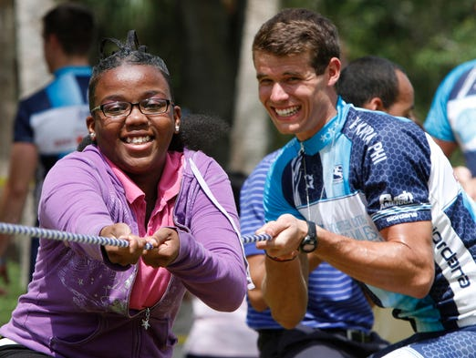Darion Young, 16, left, with help from Push America cyclist Justin Hall, plays tug-of-war with other students and cyclists at the Goodwill L.I.F.E. Academy in Fort Myers Monday, May 12.