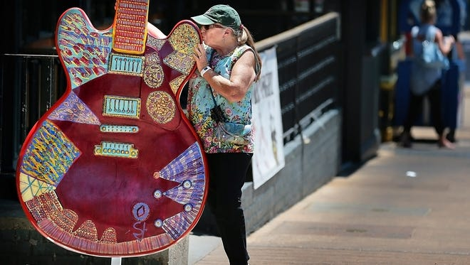 Tourist Barbara Hawthorne from Pine Harbor, Georgia shows a little affection for a piece of guitar art on Beale Street in front of Club 152 Monday afternoon. Club 152 is suing the nearby Purple Haze claiming the club should be forced to stop serving alcohol at 3 a.m. because they are  not part of the Beale Street district.