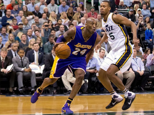 Lakers forward Kobe Bryant, left, dribbles the ball around Jazz guard Rodney Hood during the second half Monday at Vivint Smart Home Arena in Salt Lake City. The Jazz won 123-75.