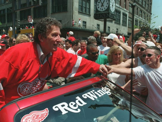In 1997, Mike Ilitch shakes hands with the parade goers