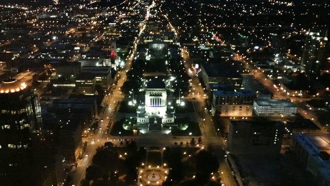 Downtown Indianapolis is aglow at dusk in this view looking north to the Indiana War Memorial and beyond, on Friday, August 7, 2015. It was taken from the 48th floor of Chase Tower, 111 Monument Circle. The prominent street lit up on the left is North Meridian and at right is North Pennsylvania Street.