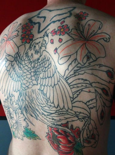 A Phoenix rising from the ashes is the centerpiece of a design on the back of Cory Adkins. The flowers honor his mother.