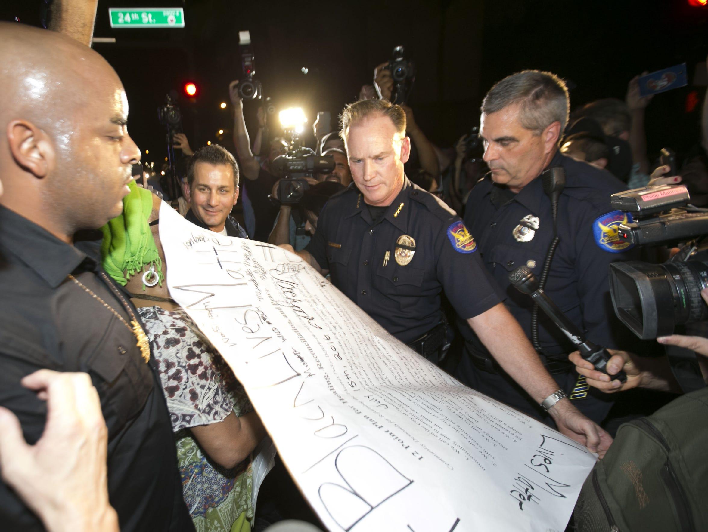 The Rev. Jarrett Maupin (left) hands Phoenix Police