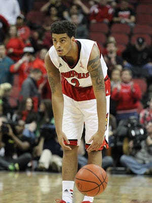 Quentin Snider dribbles the ball at half-court to end the game 80-55, Louisville coming out ontop