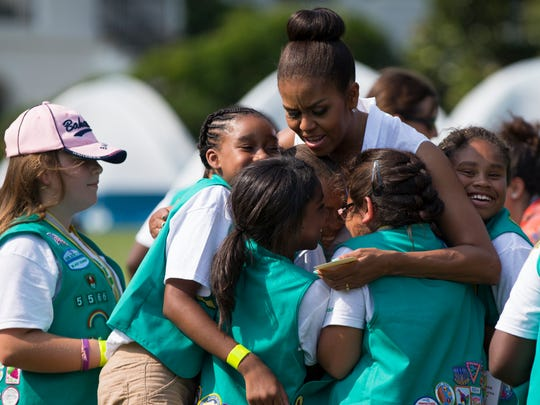 First lady Michelle Obama hugs a group of Girl Scouts