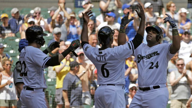 Jesus Aguilar (right) celebrates with Lorenzo Cain and Christian Yelich after Aguilar hit a three-run homer against the New York Mets during the s third inning Sunday at Miller Park.