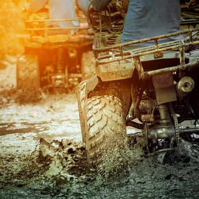 An image of an ATV rider in mud.