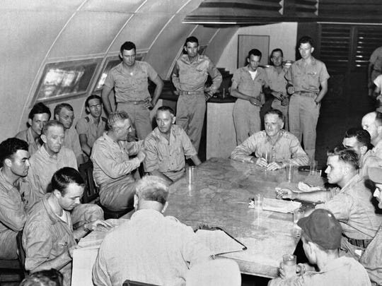 FILE - In this Aug. 6, 1945 file photo made available by the U.S. Army, the crew of the Enola Gay is debriefed in Tinian, Northern Mariana Islands after returning from their atomic bombing mission over Hiroshima, Japan. At foreground left, seated at the corner of the table, is Capt. Thodore VanKirk, navigator. Tom VanKirk says his 93-year-old father, the last surviving member of the Enola Gay crew, died at the retirement home where he lived in Georgia on Monday, July 28, 2014. (AP Photo)