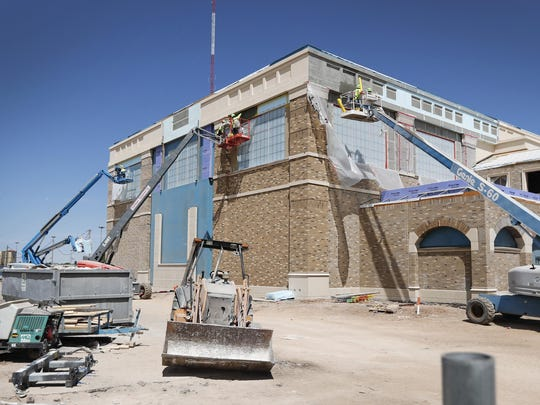 Construction workers work on the exterior of the Dustin R. Womble Basketball Center on Tuesday in preparation for applying an exterior finish. The $29.5 million project is scheduled to be complete this summer.