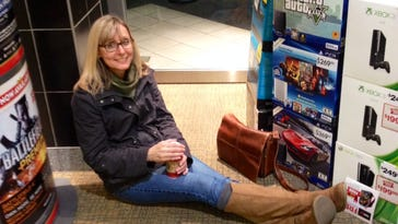 Christine Magee waits for the midnight opening at GameStop at CoolSprings Galleria on Thanksgiving evening. The retailer has announced it will close 2 to 3 percent of its stories.
