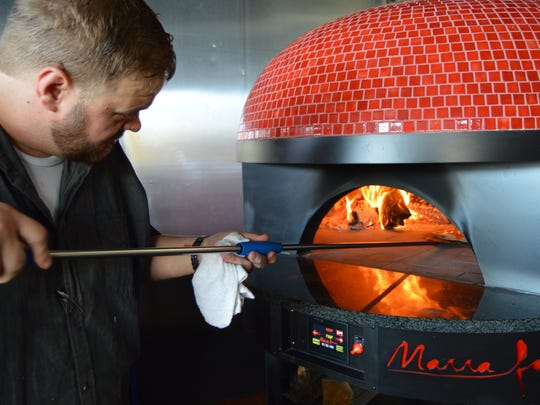 Brenton Wallace, chef and owner of Crust & Craft in Rehoboth Beach, checks on a pizza in his Marra Fornia oven.