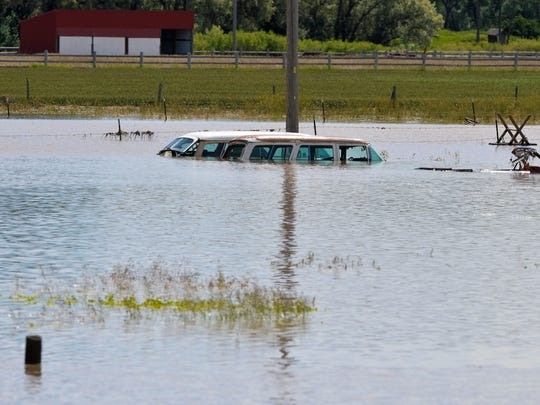 Cars submerged under Sun River floodwaters along South