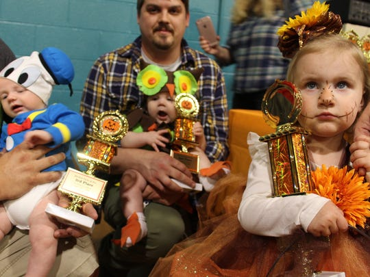All eyes were on the adorable winners of the costume contest for ages three and under, (from left) Truman Wagner (Donald Duck), third-place; Oliver McCormack (owl), second-place; and Kylie Warnock (Harvest Princess Flower), who took first-place. All winners received a trophy.