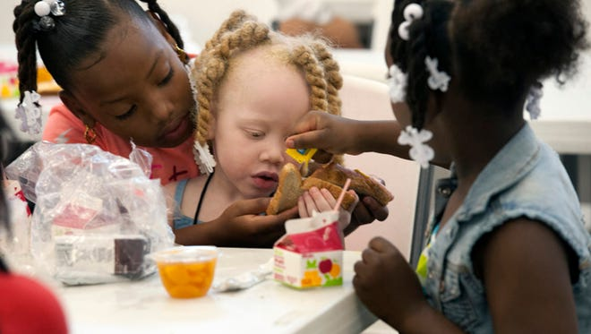Yazmonea Griffin, left, and Yurantianna Kent, right, helps Saraih Martin, center; prepare her lunch at the Ebenwood Community Center on June 2, 2015. The meals were provided to the center through the Bay Area Food Bank and its summer food program. Summer food programs in Escambia and Santa Rosa counties will be prevalent starting Monday.