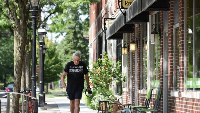 Kirk Handren walks his Monty along Agnes, a main draw in West Village, on Tuesday.