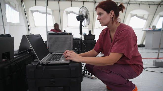 Scientist Andrea Marzi checks blood test results on Aug. 21 in a new CDC mobile laboratory near Monrovia, Liberia.