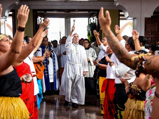 Coadjutor Archbishop Michael Jude Byrnes, center, sprinkles holy water on parishioners, as Chamorro cultural performers sing during a liturgy prayer to celebrate the beginning of his episcopal ministry, at the Dulce Nombre de Maria Cathedral-Basilica in Hagåtña on Wednesday, Nov. 30, 2016.