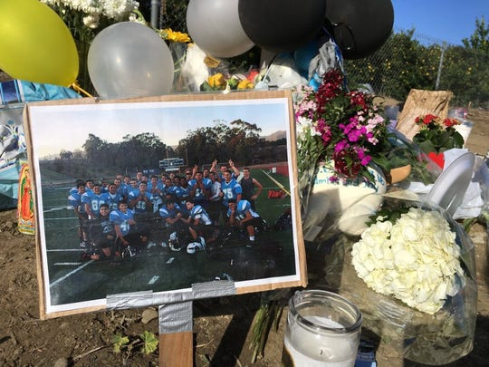 LISA MCKINNON/THE STAR   A photo of the Buena High School freshman football team is part of a roadside memorial created at Saticoy Avenue and Telegraph Road in Ventura for team member Jonathan Hernandez, 14. Hernandez was riding his bicycle early Friday morning when he was killed in a hit-and-run accident involving two vehicles.