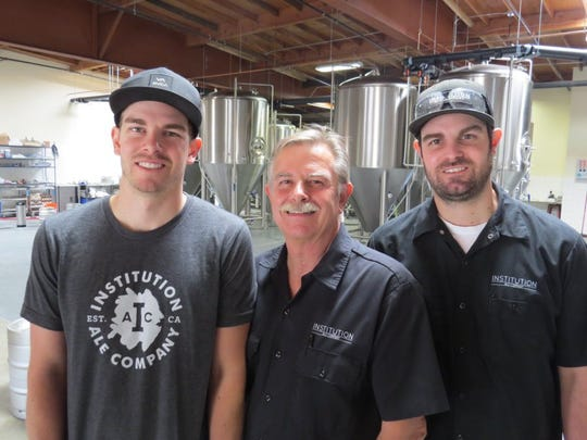 Institution Ale Co. co-owners Roger Smith, center, and sons Shaun Smith, left, and Ryan Smith, head brewer, pose at the brewery's new location on Mission Oaks Boulevard in Camarillo.