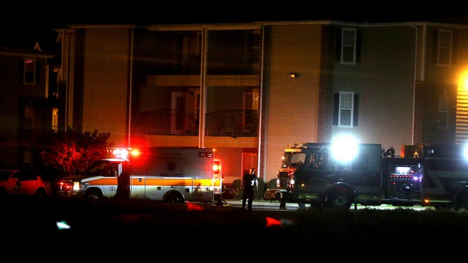 Emergency personnel work a scene of a double shooting at the University Gables Apartments early Sunday morning.