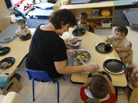 Alyssa Breitmayer feeds her class of 1-year-olds Wednesday at the Olathe Family YMCA in Olathe, Kan.