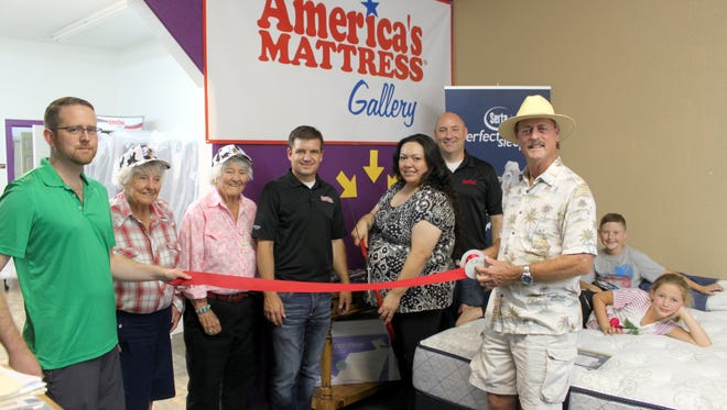 America's Mattress held its grand opening and open house on Saturday, Aug. 14, at 116 S. Gold St. Members of the Deming-Luna County Chamber of Commerce/Visitor Center were on hand for a ribbon-cutting ceremony. Doing the honors is store employee Virgie Miller, at center with scissors, and store manager Tip Barentine.