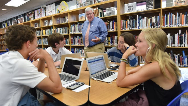 """Bruce Wachter (center), associate head of school, walks through the library to talk to students (from left) Reid Bartosch, 16, Luke Jayne, 16, Katrina Smith, 17, and Catalina Pratt, 16, as part of his afternoon routine   at St. Edward's School in Vero Beach. Wachter is retiring at the end of the school year to end his 45-year career at St. Edward's School. """"It's been very enriching,"""" Wachter said. To see more photos go to TCPalm.com."""