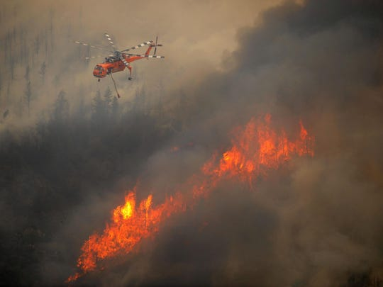 A helicopter flies through the Cache La Poudre Canyon in June 2012 as flames from the High Park Fire scorch the forest south of the river, near Fort Collins.
