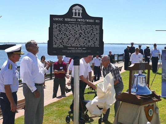 A plaque honoring the Coast Guard Cutter Sebago is unveiled during a ceremony at Plaza de Luna Saturday morning. Up until 1972 the cutter used to be docked at this spot next to the Port of Pensacola.