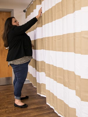 Kylie LeMaster pulls back a curtain in the withdrawal  support clinic that will be located in the basement of Friel and Associates where patients will be able to stay through the day during their detox.