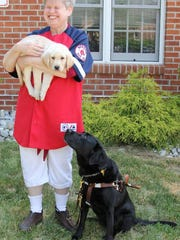 Mary Manwaring holds Ortiz, a yellow Lab, while her Seeing Eye dog, a black Lab named O'Hara, looks on.