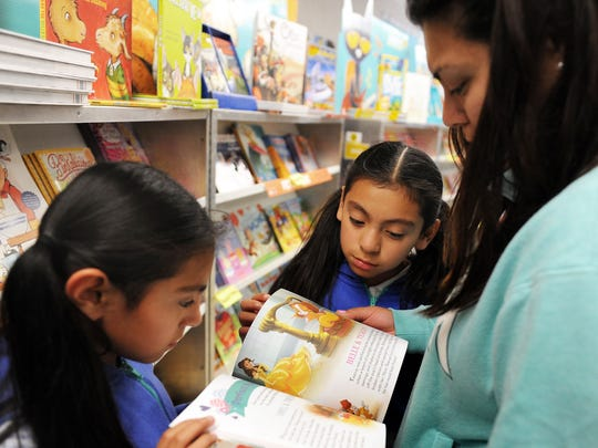 From right, mother Jacqueline Lopez checks out Palace Pets with twins Ashley, center, and Sheila at the Boronda Meadows Book Fair in Salinas.