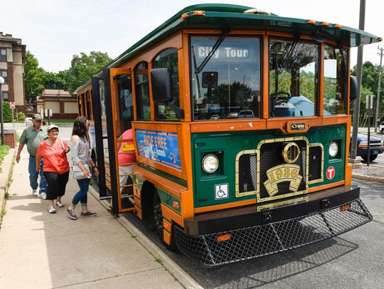 Passengers board a trolley outside the St. Cloud City