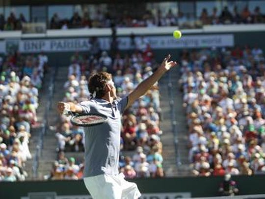 Roger Federer serves against Novak Djokovic in the 2014 BNP Paribas Open final in Stadium 1 at the Indian Wells Tennis Garden.