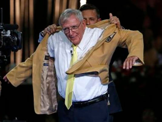 Pro Football Hall of Fame inductee Ron Wolf slips on his gold jacket with the help of his presenter and son Eliot Wolf, rear, during the Gold Jacket Ceremony in Canton, Ohio, on Thursday.